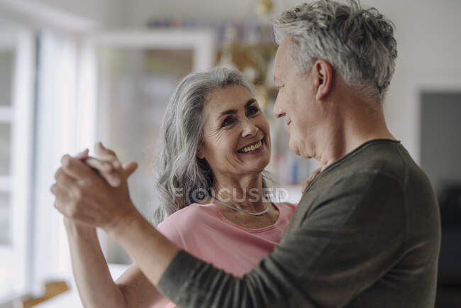 Happy senior couple dancing in living room at home — Stock Photo