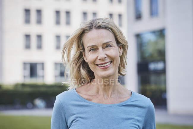 Porträt einer lächelnden blonden Frau in der Stadt — Stockfoto