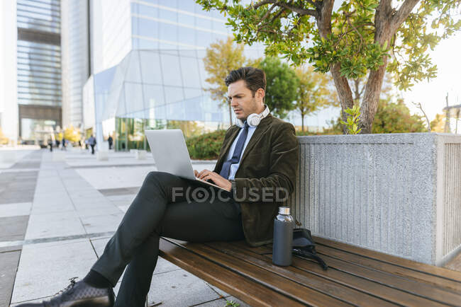 Businessman sitting on bench in the city using laptop, Madrid, Spain — Stock Photo