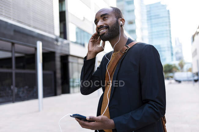 Smiling young businessman listening music with earphones and smartphone  in the city — Stock Photo
