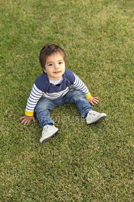 Portrait of little boy sitting on lawn — Stock Photo