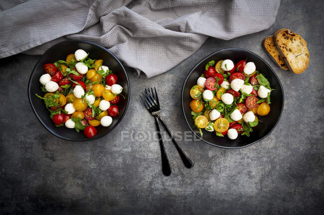 Overhead view of salad with arugula, mozzarella, cherry tomatoes and basil — Stock Photo