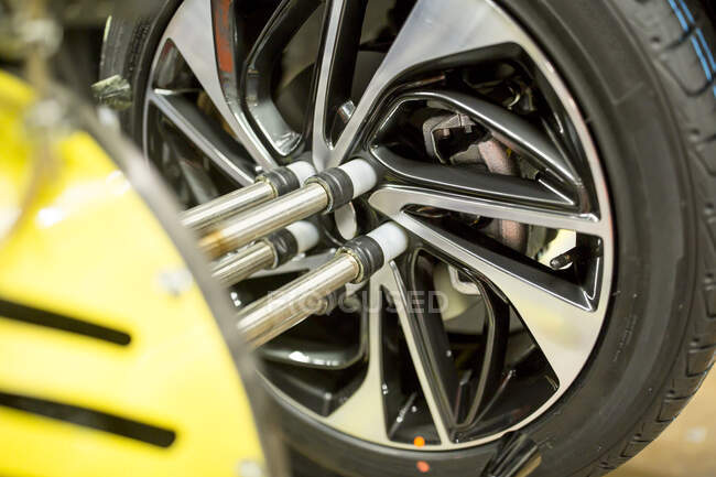 Detail of modern automatized car production in a factory, mounting of tyre — Stock Photo