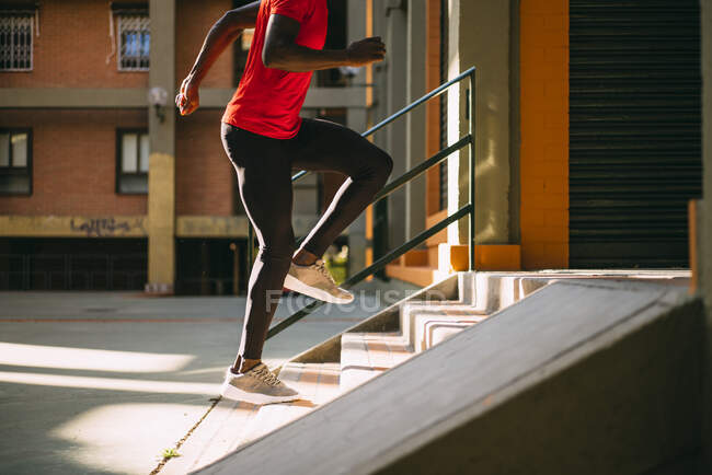 Young sportive man running upstairs on outdoor staircase — Stock Photo