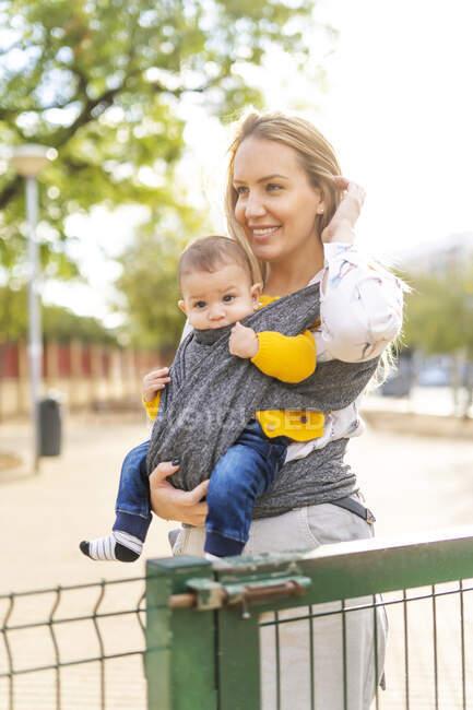 Щаслива мати носила хлопчика в санях. — стокове фото