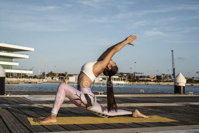 Азиатка практикует йогу на пирсе в гавани, позирует воину — стоковое фото