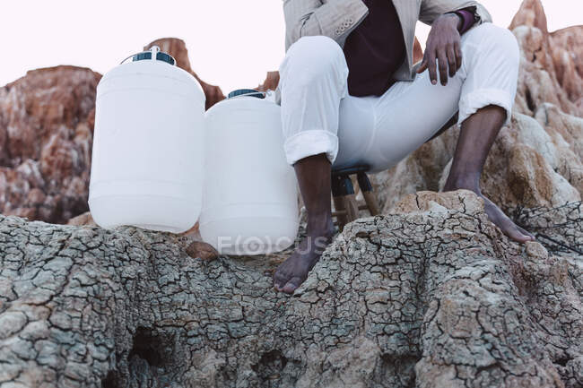 Man with empty water cans sitting on rock — Stock Photo
