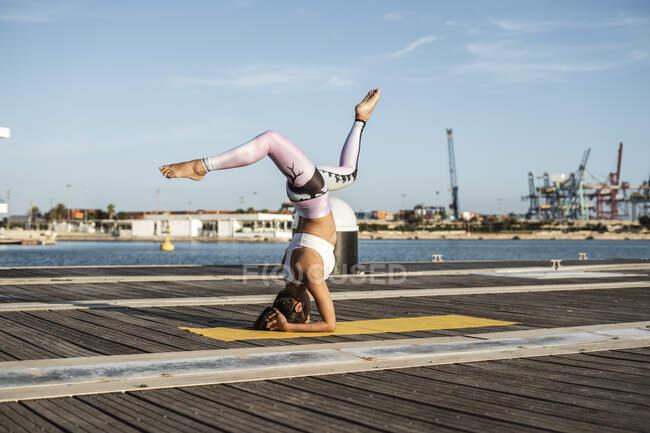 Азиатка, практикующая йогу на пирсе в гавани, стойка на голове с расщеплением — стоковое фото