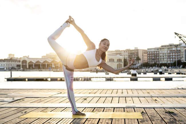 Азиатка, практикующая йогу на пирсе в гавани на закате, позирует танцовщицей — стоковое фото