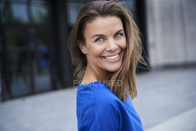 Retrato de una atractiva morena con top azul en la ciudad - foto de stock