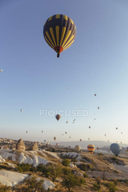 Colorful hot air balloons flying over rocky landscape at Cappadocia against clear sky, Cappadocia, Turkey — Stock Photo
