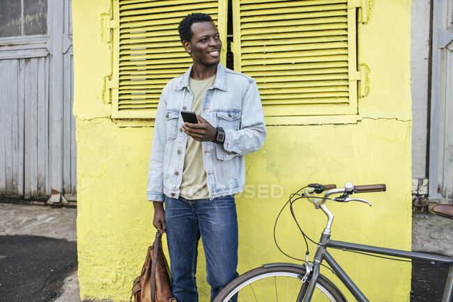 Молодий чоловік з смартфоном чекає перед жовтим конвертом. — стокове фото