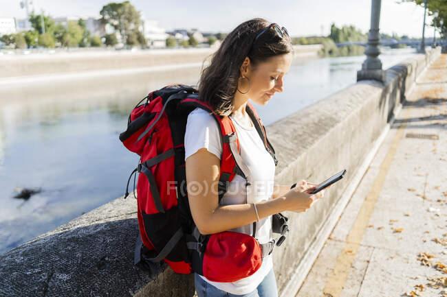 Молода жінка - рюкзак за допомогою смартфона в річці Верона (Італія). — стокове фото