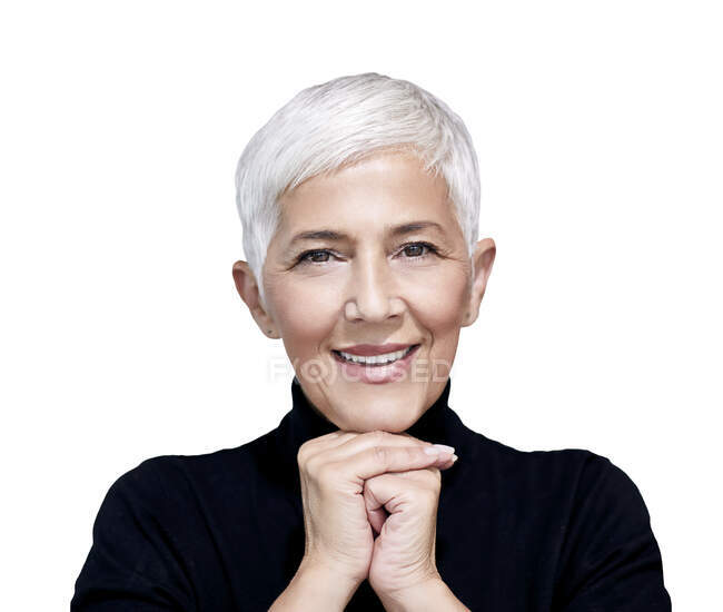 Portrait of mature woman with short grey hair wearing black turtleneck pullover against white background — Stock Photo