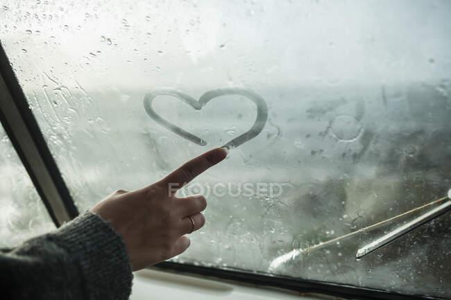 Dedo de mujer dibujando un corazón en la ventana de una furgoneta - foto de stock