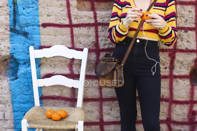 Mujer pelando mandarina, vista parcial - foto de stock