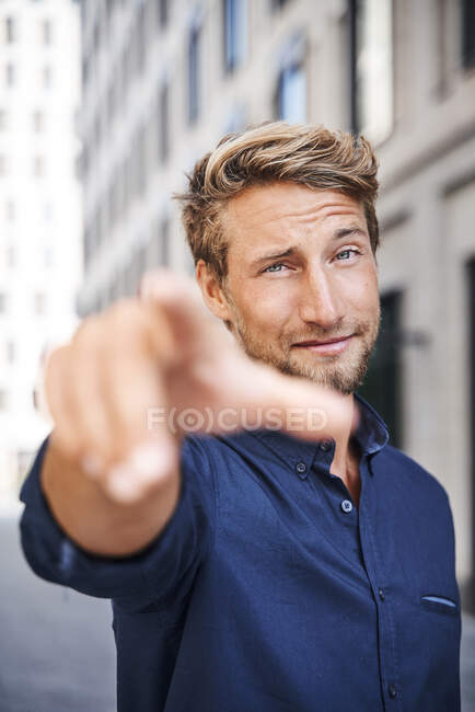 Portrait of confident young man in the city pointing his finger — Stock Photo