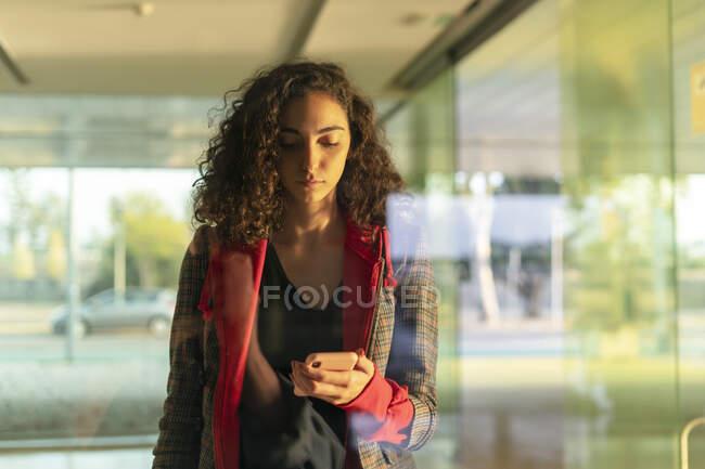 Retrato de jovem mulher atrás do painel de vidro olhando para o telefone celular — Fotografia de Stock