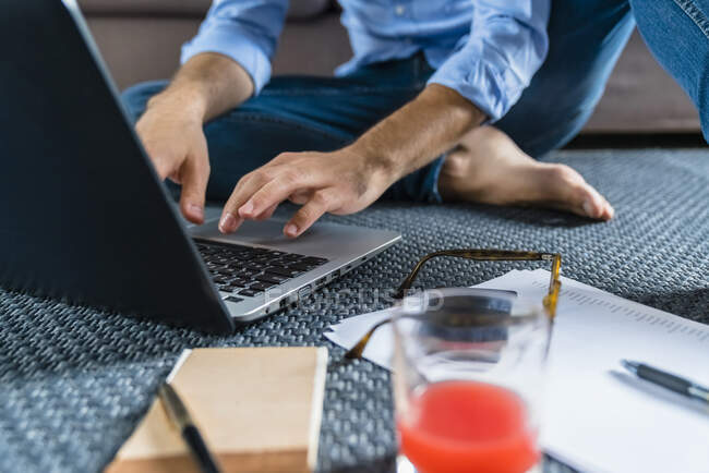 Young man sitting on the floor at home using laptop, partial view — Stock Photo