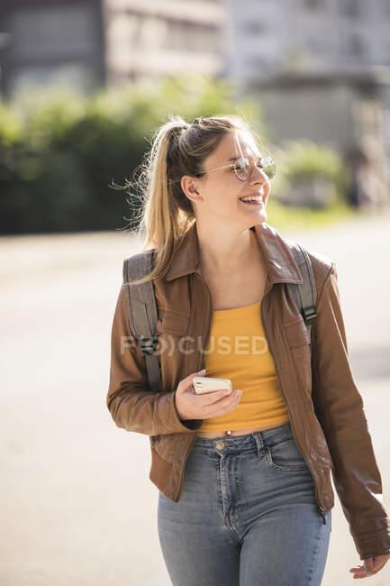 Mujer joven sosteniendo el teléfono inteligente y mirando hacia los lados - foto de stock