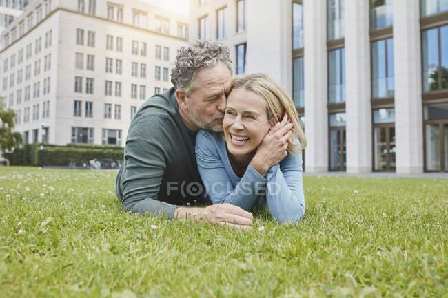 Pareja madura feliz acostada en el césped de la ciudad - foto de stock