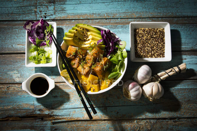 High angle view of poke bowl with ingredients on wooden table — Stock Photo