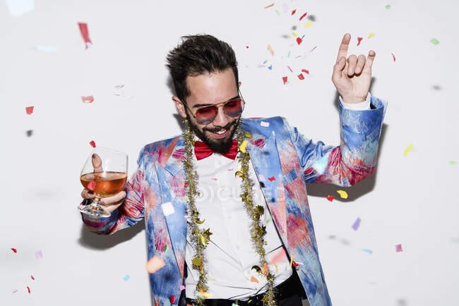Uomo fresco ed elegante indossa un abito colorato e occhiali da sole che ballano a una festa — Foto stock