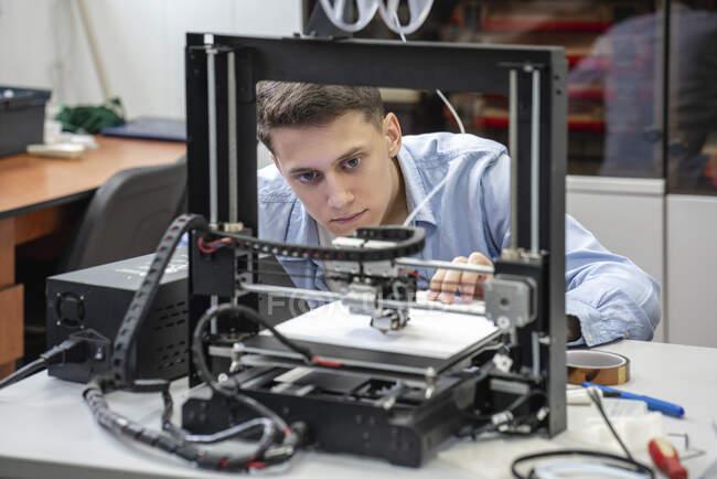 Étudiant configurant une imprimante 3D — Photo de stock