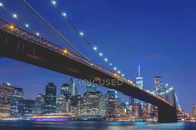Estados Unidos, Nueva York, Nueva York, Brooklyn Bridge y Manhattan iluminados por la noche - foto de stock