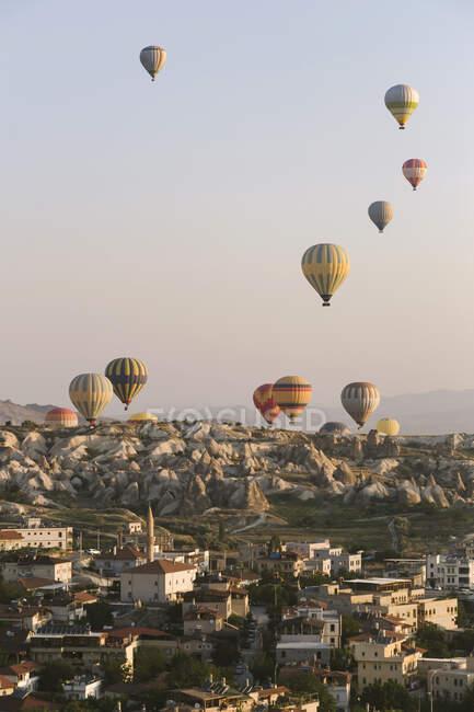 Барвисті повітряні кулі, що літають над будівлями над чистим небом у національному парку Ґореме (Каппадокія, Туреччина). — стокове фото