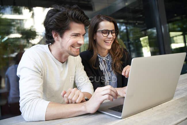 Щасливий бізнесмен і бізнесменка з лептопом на зустрічі в місті. — стокове фото