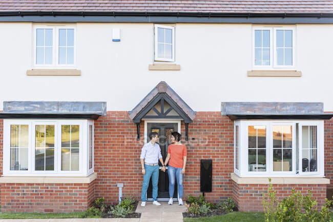Couple standing at doorstep of their home — Stock Photo