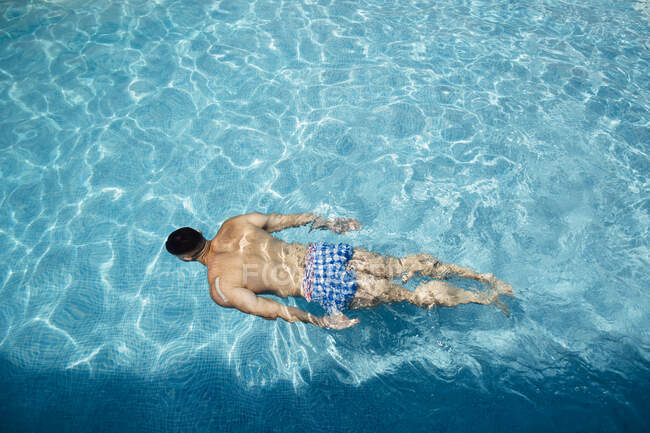 Back view of man floating in swimming pool — Stock Photo