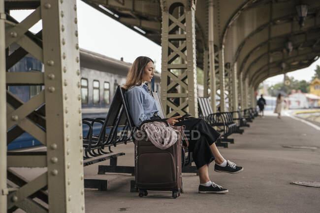 Joven viajera esperando en la estación de tren, usando e-book - foto de stock