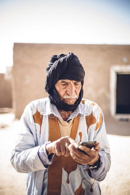 Senior man using cell phone in Smara refugee camp, Tindouf, Algeria — Stock Photo