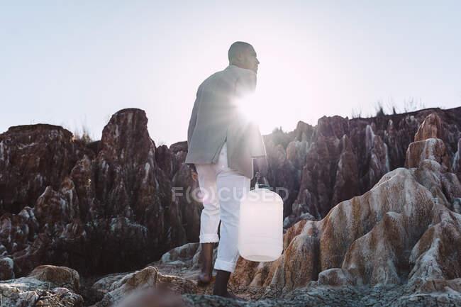 Молодий чоловік, який тримає порожнечу, шукає воду в пустині. — стокове фото