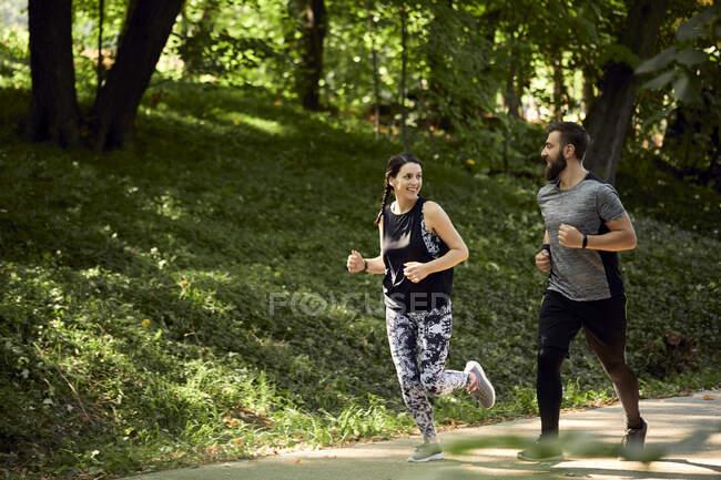 Pareja deportiva corriendo por el camino del bosque - foto de stock