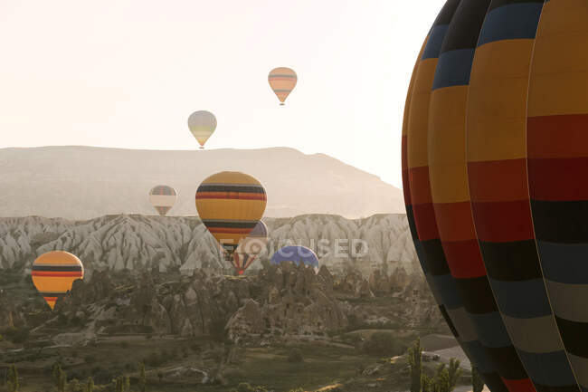 Colorful hot air balloons flying over mountains at Goreme National Park during sunset, Cappadocia, Turkey — Stock Photo