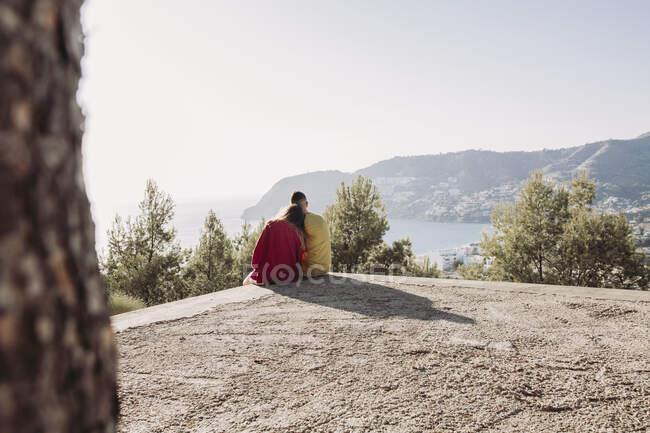 Giovane coppia seduta sul punto di vista — Foto stock
