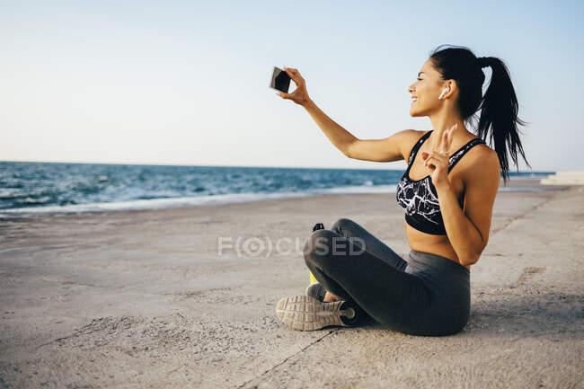 Женщина использует смартфон и делает селфи, сидя на пирсе — стоковое фото