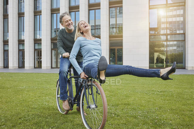 Exuberant mature couple riding bicycle on lawn in the city — Stock Photo