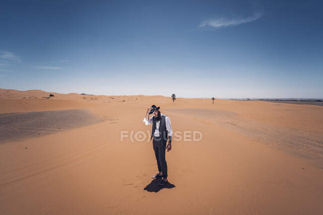 Man with a beard and hat in the dunes of the desert of Morocco — Stock Photo
