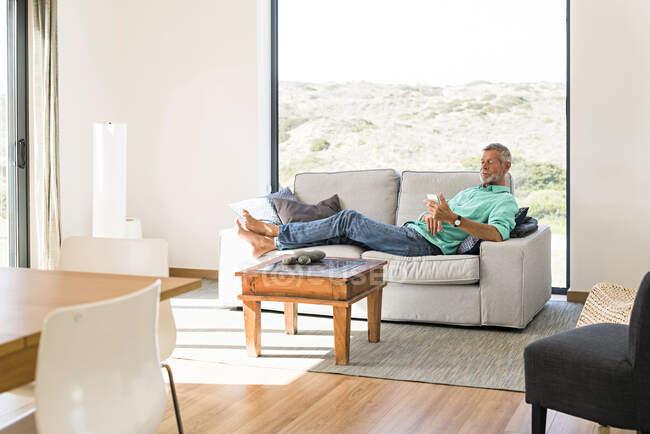 Старший на дивані користується мобільним. — стокове фото