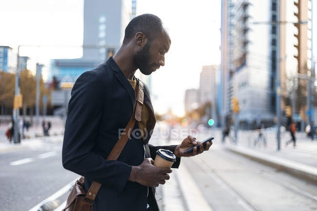 Young businessman with coffee to go looking at smartphone — Stock Photo