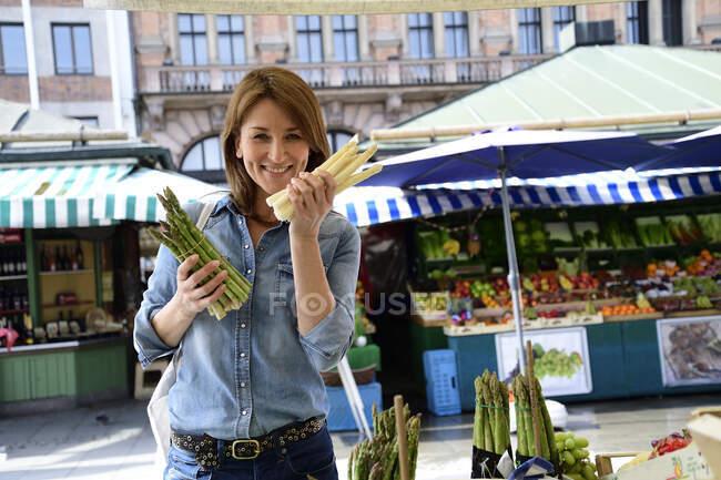 Retrato de mulher madura sorrindo escolhendo espargos em uma barraca de mercado — Fotografia de Stock