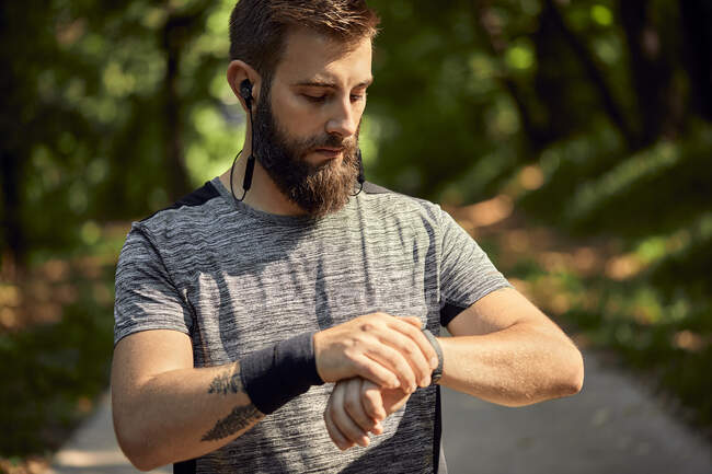 Portrait of sporty man with earphones in forest checking his smartwatch — Stock Photo