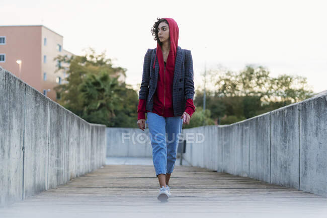 Portrait of young woman walking on bridge looking at distance — Stock Photo