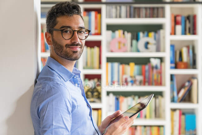 Portrait of smiling young man standing in front of bookshelves at home with digital tablet — Stock Photo
