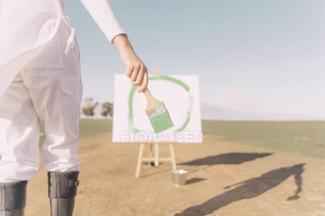 Mujer joven en el campo seco, pintando lienzo con pintura verde - foto de stock