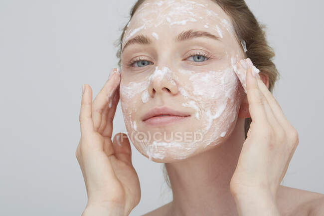Portrait of blond young woman applying cream on her face — Stock Photo